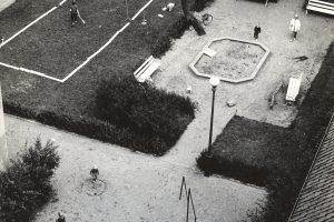 Översikt över Kronhusparken där två pojkar spelar badminton och en mamma med barn står vid en sandlåda.