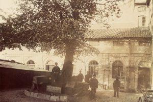 Fyra män står och en man sitter under ett träd på Hallska teaterns innergård.