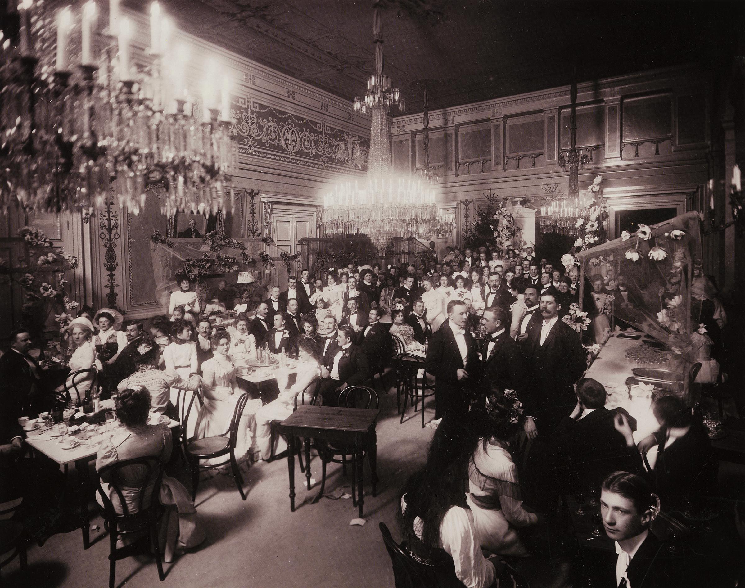 Uppklädda människor har samlats inne i Börsens festsal år 1895.