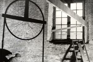 En man sitter på golvet i Kronhuset och bilar ett hål i väggen.