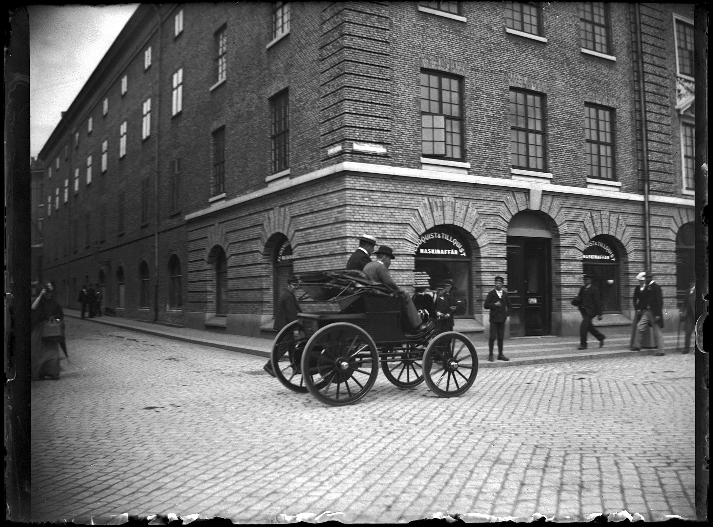 Två män åker i en äldre bil år 1900 medan människor står utmed gatan och kollar på.
